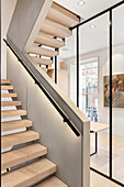 Indirect lighting below handrail of staircase with open treads