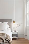 Golden pendant lamp above bedside table in bedroom