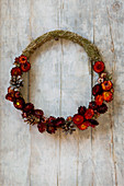 Wreath of hay with red everlasting flowers and pine cones