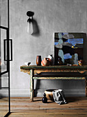 Rustic wooden table with ceramics and painting against gray wall