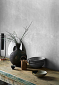 Ceramic bowls and vase on rustic table against gray wall