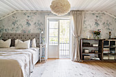 Vintage-style bedroom with sloping ceiling and balcony