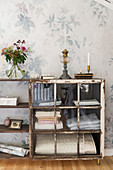 Vintage-style display case made from shelved and old window against floral wallpaper