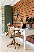 Desk and old swivel chair against rustic log-cabin wall