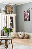 Old cupboard and rustic accessories in living room with grey walls