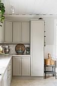 Klassische Einbauküche im Landhausstil mit hellgrauen Fronten