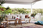 Cushions on wooden bench, stool and rattan chair on terrace