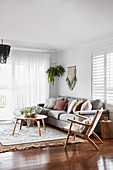 Scatter cushions on pale grey sofa, armchair and coffee table in living room