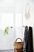 Towels hung from hooks and basket below extravagant necklace hung on wall