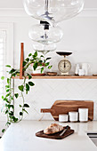 L-shaped kitchen counter below houseplants and vintage scales on shelf