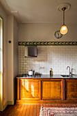 Küchenzeile aus Holz mit Schiebetüren im Altbau mit Stuck