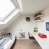 Cot and desk in white attic room