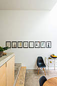 Collection of pictures on white wall of open-plan kitchen