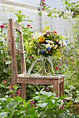 Summer bouquet standing on chair in greenhouse