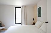 Schlicht gehaltenes Schlafzimmer in weiß und Naturtönen