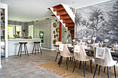 Set dining table with upholstered chairs in front of monochrome mural wallpaper
