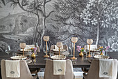 Festively set dining table with upholstered chairs in front of monochrome mural wallpaper