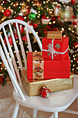 Festlich verpackte Weihnachtsgeschenke auf weißem Stuhl