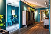Hallway with dark wooden floor and turquoise walls