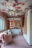 Girl's bedroom decorated in pink with floral wallpaper on ceiling, cubby bed and bookcase