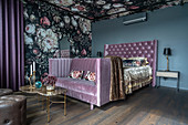 Double bed and bedroom sofa against dramatic floral wallpaper in bedroom