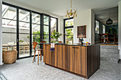 Elegant island counter with wooden front next to terrace doors