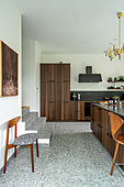 Elegant, custom kitchen and island counter with wooden fronts in split-level house