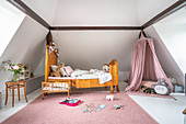 Antique wooden bed and play area with canopy in girl's bedroom