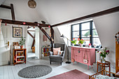 Pink sideboard and armchair in girl's attic bedroom