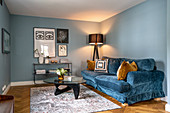 Blue velvet sofa, standard lamp and coffee table in room with blue walls