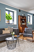 Grey sofa set, coffee table and retro dresser in living room with blue wall
