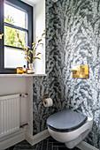 Toilette mit Fenster und grau gemusterter Tapete