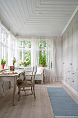 Desk below conservatory windows and fitted cupboards in country-house style