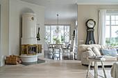 Round tiled stove in open-plan, Scandinavian-style interior
