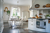 Open-plan, country-house-style kitchen-dining room with stone floor