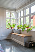 Bench below windows in hallway with wood-panelled walls