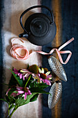 Black teapot, ribbons, glass, pine-cone Christmas-tree decorations and Echinaceas