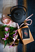 Black teapot, ribbons, Echinaceas, book and cross-stitch mobile phone case