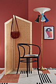 Handcrafted, Viennese cane screen, chair and standard lamp against red-painted wall