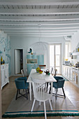 Dining area in white country-house kitchen with wood-beamed ceiling