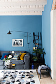 Grey sofa in living room with blue wall and white wood-beamed ceiling