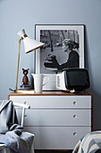 Black-and-white photo, TV and table lamp on top of chest of drawers