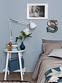 Reading lamp on bedside table next to bed in bedroom with blue-grey wall