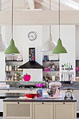 Island counter in open-plan kitchen with hot pink and pale pink accents