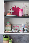 Feminine crockery and kitschy accessories on kitchen shelves