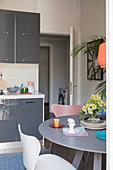 Runder Esstisch in kleiner Wohnküche mit grauen Fronten