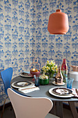 Round, set table and designer chairs in front of blue-and-white wallpaper