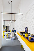 Open-plan kitchen and dining area with blue and yellow accents in Italian period building