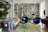 Floor-to-ceiling bookcase, sofa and blue velvet armchairs in eclectic living room