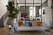 Blick vom Wohnbereich mit Sofa in die Küche abgetrennt durch raumhohe Glaswand